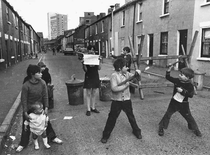 """The Belfast girl holds up a sign which I think reads, """"NO ENTRY"""". The caption of this press photo read, """"The Tragic Routine of Belfast: Belfast 1972--where barricades -- and bomb blasts -- are almost commonplace. The young children play a game of their own: the threat of real violence is never far away. Will their generation grow up into a Belfast of peace. -- or continuing bloodshead? Source: Camera Press."""