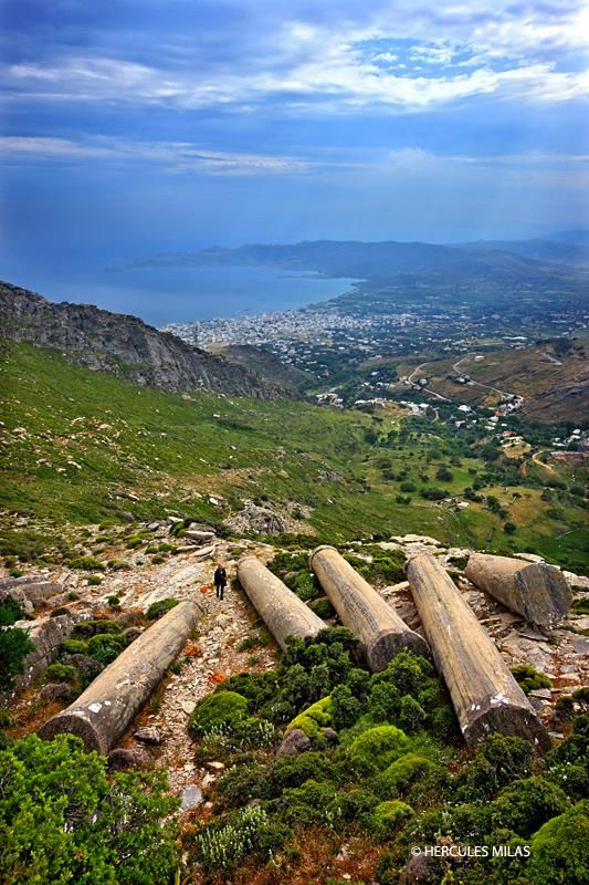 """Forgotten ancient columns at an ancient quarry on the slopes of Mount Ochi (""""Oche""""), about an hour walk from Myloi village. In the background you can see the town and the bay of Karystos. Evia (""""Evvoia"""") island, Central Greece."""