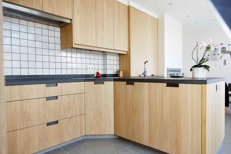 Tijdloze eiken keuken met vlakke fronten. De hoeken zijn afgeschuind met een carrousel om de kleinere ruimte maximaal de benutten
