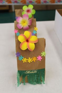 """Goodie bags: daughter's """"hula girl"""" 1st birthday baby luau. Plumeria hair clips from local swapmeet, brown lunch bag, flower cutouts and sparkly fringed tissue paper!"""
