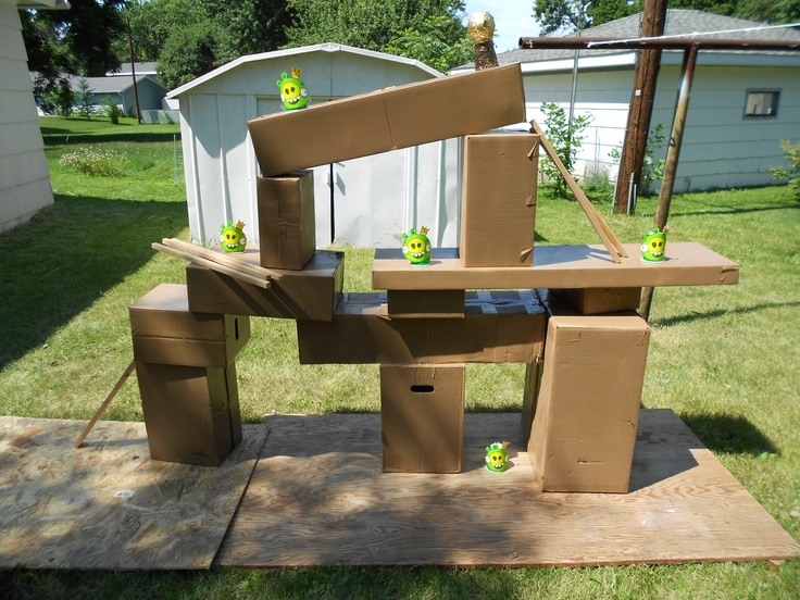 Angry bird outdoor life size game. Spray paint boxes brown, pigs are cut out party plates from Party city, and they are taped to a cup so they hold up better. Used a sling with water balloons to knock the pigs down