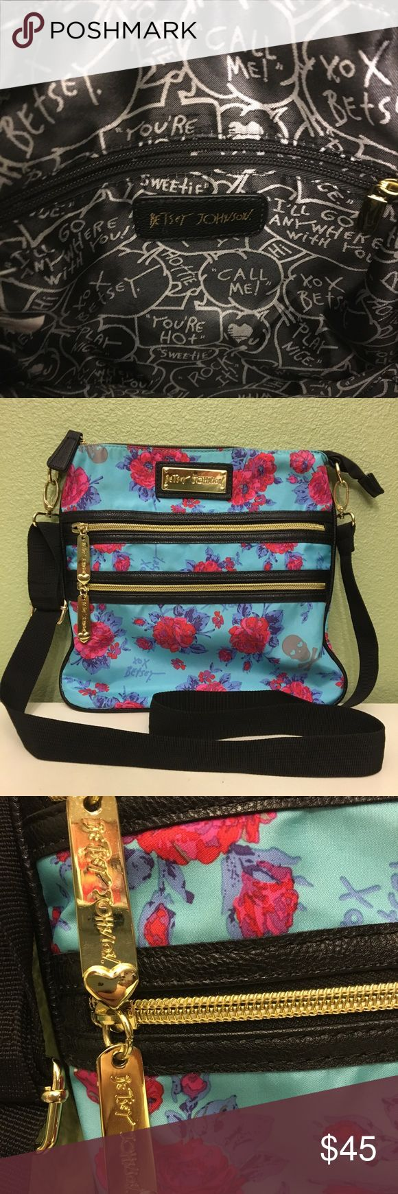BETSEY JOHNSON cross body bag w/plastic tag tag BETSEY JOHNSON brand cross body bag. It is also adjustable and be a shoulder bag if you desire. It is a light blue and has an assortment t or red/pink flowers, darker blue leaves, XOX BETSEY's signature and gray skull and crossbones. The front of the bag has not one but two gold zippered pockets and the inside is black with a zipper pouch on one side and two elastic pockets on the opposite.  The plastic tag holder is still attached but the…