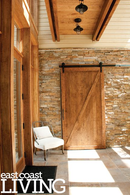 This custom-built sliding barn door separates the garage and guest bath from the entry into the main house. Featured in the Summer 2012 issue of East Coast Living. Photo by Joanna Nickerson, Studio Rouge