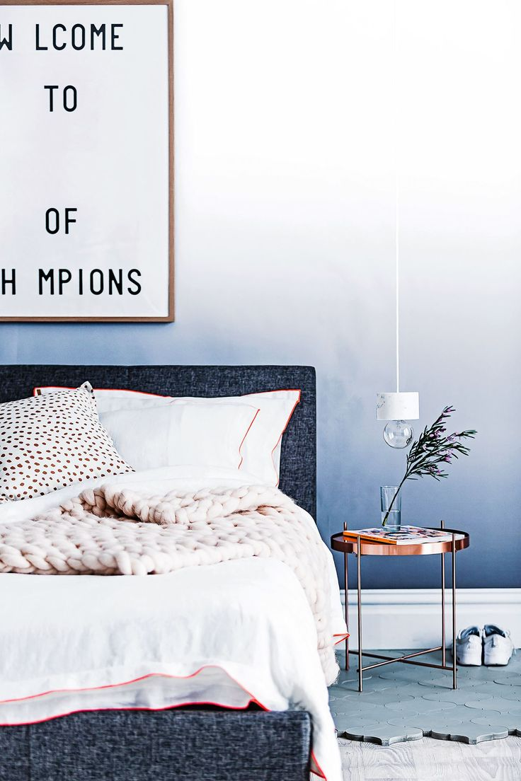 Bedroom: exposed lightbulb bedside pendant light with marble base, charcoal fabric upholstered bed and bedhead, white bed linen, copper round bedside table, blue Moroccan floor tiles laid over pale limewashed timber floorboards