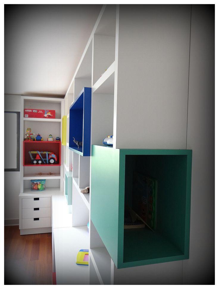 Mueble biblioteca enchapado blanco, con aplicaciones de cajones en colores fuertes. Sistemas de cajones profundos para guardado de juguetes y cajones basicos. Sin tirador, con cortes rectangulares como manilla. Dos cajas en treillage para guardado de objetos. Rieles telescópicos, enchape lamitech.