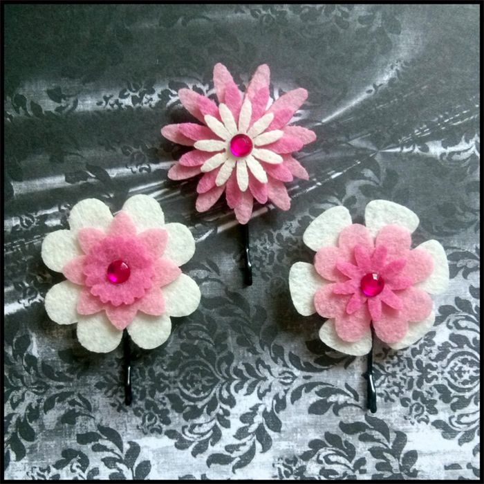 3 piece set of layered felt flowers in pink and cream on bobby pins. This delicate trio of layered felt flowers in gorgeous shades of pink and cream are delightfully decorated with dark pink rhinestone centres.1 Set Available. $5.00 for the set.