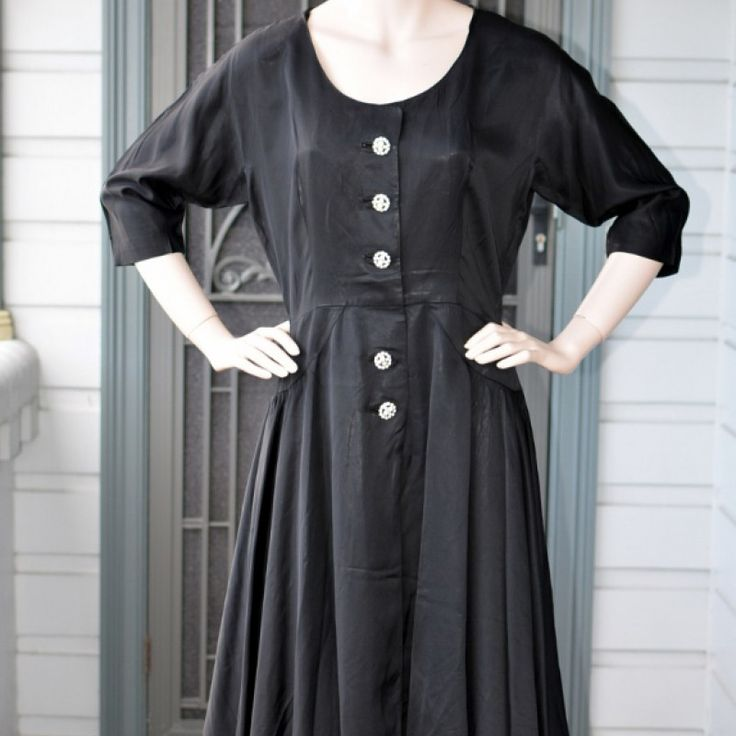 1950s Rhinestone Black Beauty Dress on Velvet Rose's Pin Up Dressing Room  Original 50s Satin Black Dress Lovely understated elegant dress. Black low sheen satin with a cotton underskirt. The buttons are the statement on this dress. 6 rhinestone buttons down the front. Made in the USA by Helen Nash Fitted bodice, waist, round neckline and elbow length sleeves. Little hip accents keep the bulk of the skirt flare over the hips and not at the waist, giving a sleeker look. The hip measurement is…