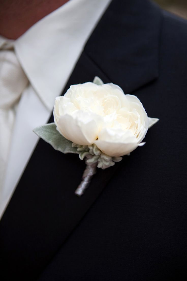 White Peony Boutonniere for groomsmen with a cobalt blue color ribbon tied to stem only partially wrapped.