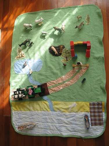 a play farm blanket...add plastic trees, wagons, animals, or military figures for realistic battles etc. fun!
