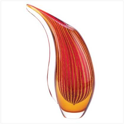 """UPC: #13907 A sparkling freeform vase celebrates the beauty of an autumn sunset, setting your surroundings alive with vibrant color. This abstract artwork is lovely alone, but especially stunning when filled with a graceful bouquet! Decorative purposes only. Each piece is individually hand-crafted for its unique beauty Weight 6 lbs. Glass. 7 1/2"""" x 3 1/2"""" x 12 1/4"""" high. $55 (plus tax/shipping). - to place an order for this product, contact us at asimpletouchgallery@gmail.com"""