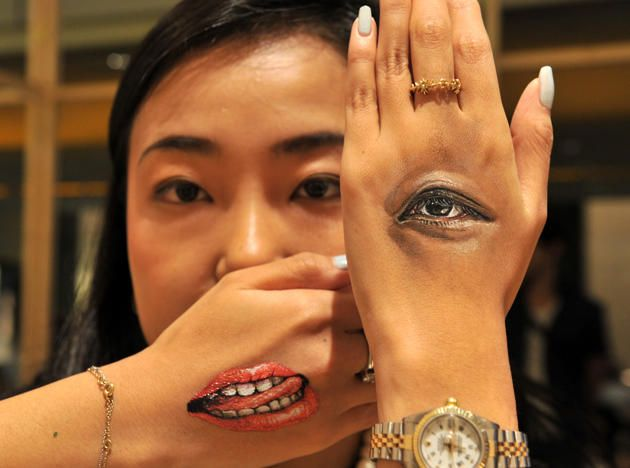 """A woman displays body-paintings of her eye and her mouth on the back of her hands after Japanese body-painting artist Hikaru Cho (unseen in this picture) painted at an art event called """"Future en-nichi"""" in Tokyo on August 6, 2014. En-nichi is a popular Japanese summer festival and 12 contemporary artists exhibit through to August 10"""