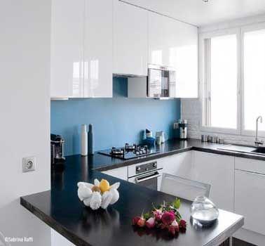 Miser sur une couleur déco pour agrandir une cuisine. Et la crédence cuisine est le bon support. Dans cette cuisine blanche, la peinture bleu posée en crédence augmente l'impression de profondeur
