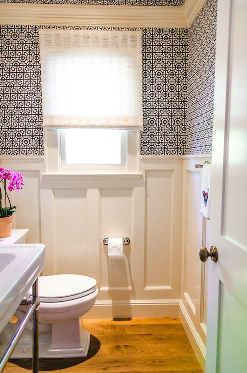 source: Evars and Anderson    Lovely powder room with white recessed panel wainscoting on lower wall. A blue and white geometric print wallpaper covers the upper half of the powder room wall as well as the ceiling. A polished chrome based washstand sits beside the toilet. A gauzy white fabric blind dresses the window.