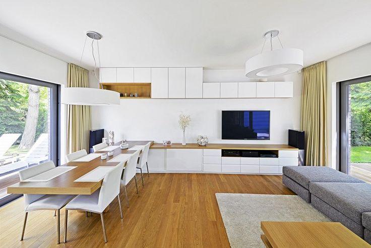 """Díky prosklení ze dvou stran má obývací pokoj dostatek světla po celý den. Dominuje mu atypická nábytková sestava na čelní stěně, z níž jako """"prodloužená ruka"""" vybíhá velký stůl pro společné rodinné stolování."""