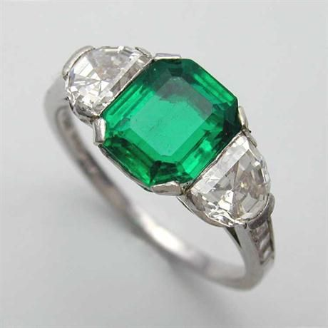 A Tiffany Art Deco three stone emerald and diamond ring, the octagonal step-cut emerald weighing 1.19 carats flanked by two half moon shape faceted diamonds weighing 0.95 in total, all set in platinum, signed Tiffany, circa 1920.