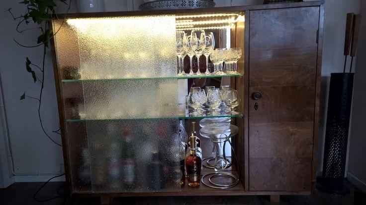 Vanha kaappi sai uuden elämän baarikaappina. Hyllyt vaihdettiin lasihyllyihin, takalevyyn liimattiin peilit ja kansilevyyn ledvalonauha. Vanhat lasiovet saivat jäädä. Valo siilautuu niiden läpi kauniisti ja kaappi toimii myös tunnelmavalona.