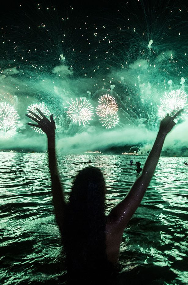 Swimmers watch fireworks during a New Year's celebration on Copacabana Beach in Rio de Janeiro on Jan. 1, 2014.