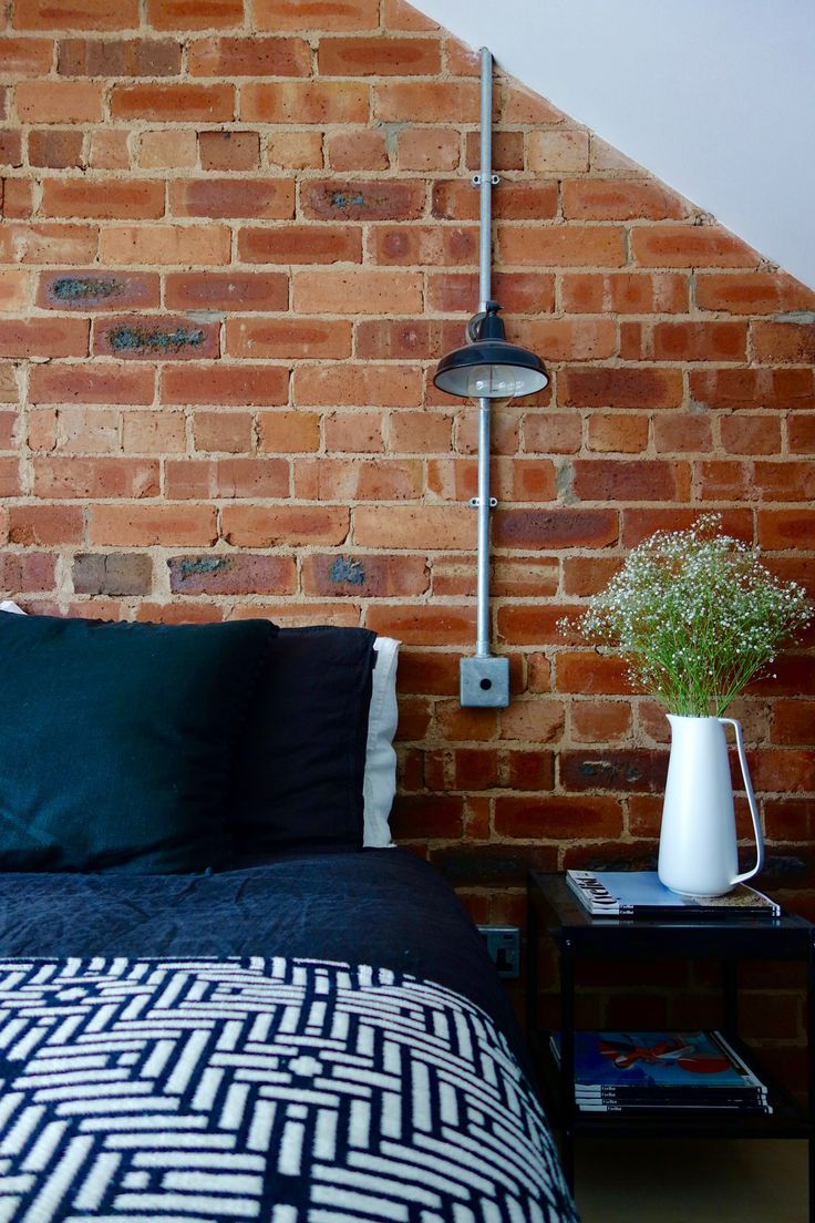 Exposed brick wall and conduit lighting. The final reveal of our loft bedroom can be seen on the blog. Interior Design by Making Spaces