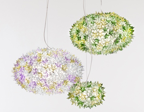 Bloom lamps by Ferruccio Laviani   Do you like the idea of having a fl oral arrangement above the table? Today the Bloom lamp family with its  distinctive original structure covered by sparkling polycarbonate fl owers as pure and precious as crystal  takes on a new elliptical shape in two different sizes and with new functions: it can be hung or used as a  wall light or ceiling fi xture.