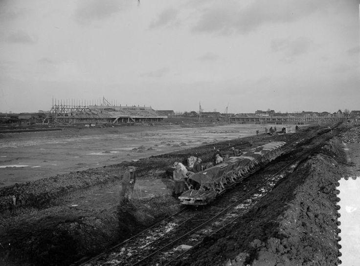 11 februari 1937 - De Bosbaan wordt gegraven in het Amsterdamse Bos. Links de tribunes, rechts het botenhuis, beide nog in aanbouw. Vanaf 1934 werden werklozen ingezet en werd de aanleg van het Bos en de Bosbaan gezien als een werkverschaffingsproject. Na de crisisjaren werkten gevangenen verder in het Amsterdamse Bos. De aanleg werd na de oorlog door gemeentewerkers voltooid en de klus was klaar in 1964. De Bosbaan werd in 1937 in gebruik genomen.