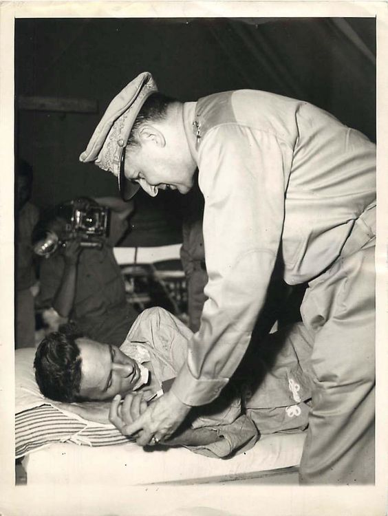 Gen. Douglas MacArthur visits Vern Haugland, war correspondent who fought his way out of the New Guinea jungle after being lost for 43 days.