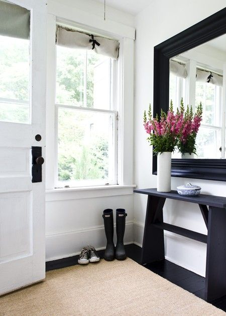 Airy Cottage Entryway...  Use inexpensive roman blinds and hold open with black ribbon.  The linen fabric was attached to tension rods for an easy window treatment option. An affordable sisal remnant is a smart choice that adds texture to this entrance. Using an inexpensive mirror, Utility room/Back door? such as this large black mirror, a steal at only $50, visually doubles the space of rooms.