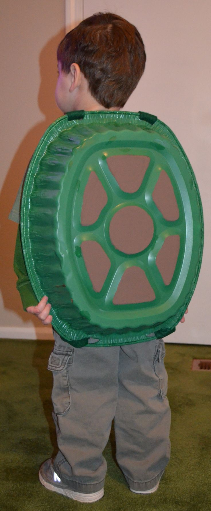 "DYI turtle shell costume for children. Just need a disposable roasting pan, spray paint, felt,and Velcro. ( I cut a sheet of felt into two thin strips and used Velcro to make the straps which criss crossed in the front and made a ""X"" shape on his chest)"