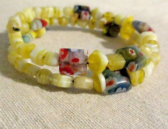 The speed of light (in meters / second) is spelled out in yellow and white Czech glass, with multicolored flowery glass pillow beads act as spacers in between each digit.