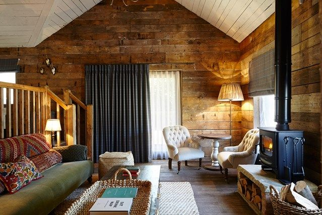 Cabin-style living room at Soho House's Farmhouse. Featuring a wood burner, antique-style armchairs and sofa with crochet detail. HOUSE - design, food and travel by House & Garden.