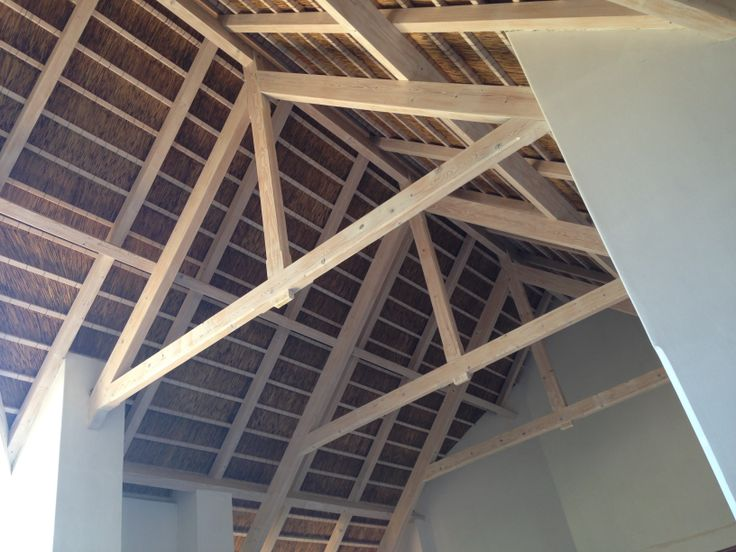 Contemporary thatch roof for a Cape vernacular style farm house, spruce trusses with a lime washed finish.