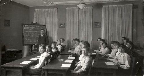 Administratieve opleidingen : Meisjes / leerlingen in een klaslokaal van het instituut Schoevers waar Franse les wordt gegeven. Nederland, Amsterdam, 1916.