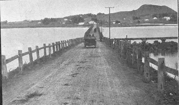 1913. Looking across the Manukau Harbour from Onehunga towards Mangere showing a car crossing the old Mangere Bridge and Mangere mountain (right background). Looking across the Manukau Harbour from Onehunga towards Mangere showing a car crossing the old Mangere Bridge and Mangere mountain (right background).