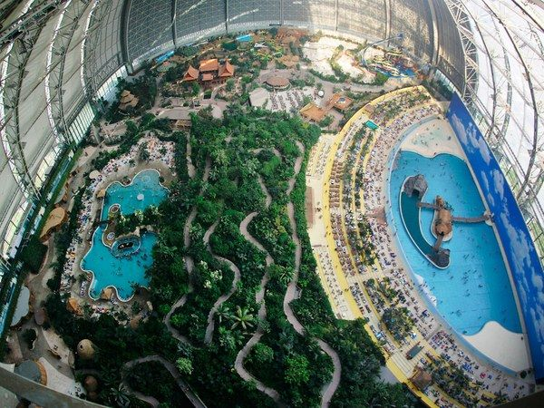 """We wouldn't think to add a visit to a waterpark onto a trip to Germany, but Tropical Islands Resort—an hour south of Berlin—looks truly tempting. Housed in a biodome, Europe's largest tropical spa and sauna complex (over 100,000 square-feet) is anchored by real sandy beaches and turquoise wading pools—plus an entire wing dedicated to the """"art of the sauna."""" Yes, please."""