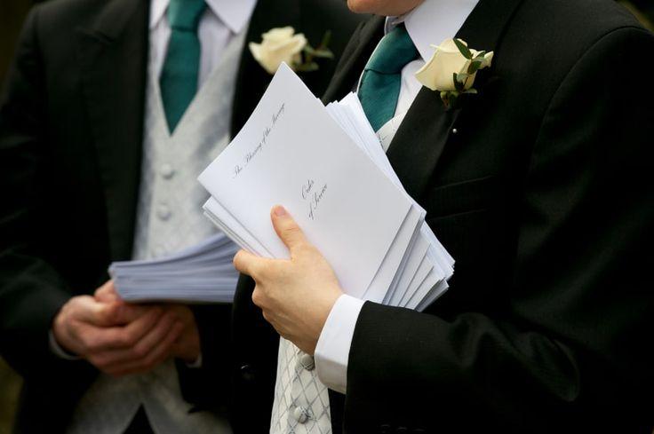 Wedding ushers holding Order of Service booklets