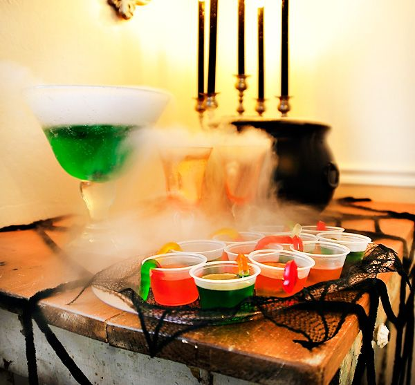 Halloween Drink Station with a cauldron of foggy witches brew, crystal goblets and gummy worm jello shooters, set upon a velvet spider web