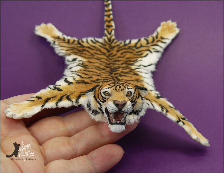 Dollhouse Miniature scale Tiger Skin Rug. Head, paws & claws freehand sculpted from polymer clay adhered to a thin leather backing with applied alpaca fibers.