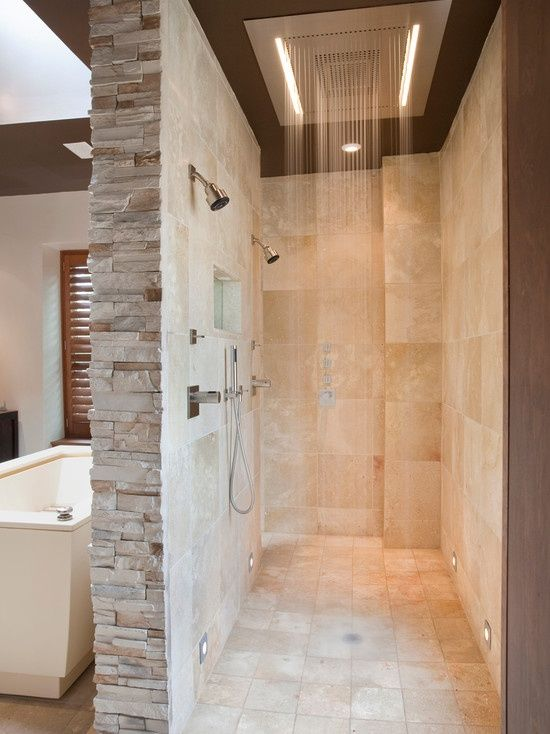 This stunning shower is surrounded by creamy marble walls and features a rain shower head in the center of the ceiling. Dual shower heads and a small window in the wall complete this room.