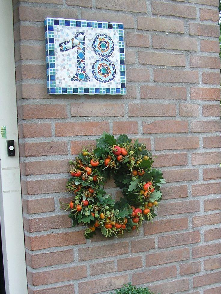 krans van eikenblad en rozenbottels bij onze voordeur