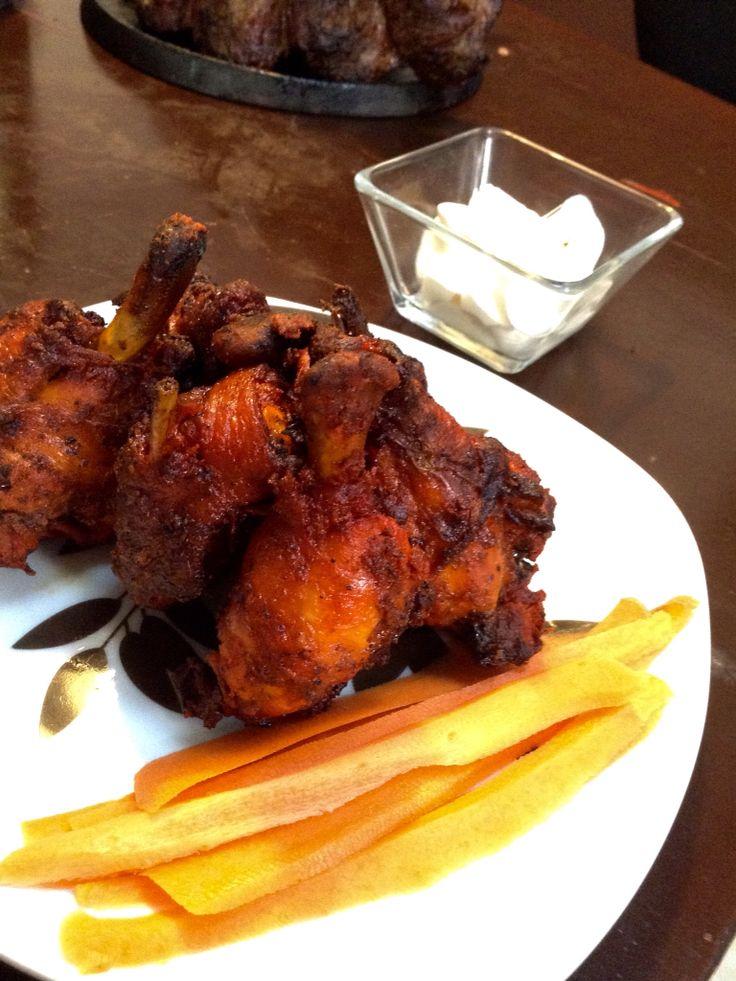 Alitas de pollo envueltas en tocino con salsa Picante y mantequilla. Aderezo de crema ácida y corazón de alcachofas, complemento de zanahorias en tiras delgadas.