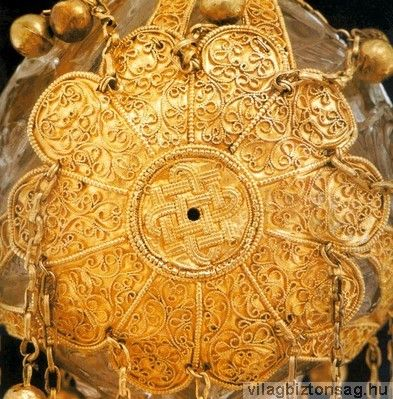 A koronázási jogar felülnézeti képe. Középen a Tejútnak is megfelelő szimbólummal a végtelen csomóval, a csomó közepén a Szent Korona tetejével megegyezően lyuk található. A tudományban viták folynak arról, hogy pontosan mi is van a Tejút magjának közepén. Több elmélet szerint egy fekete lyuk, mely körül új csillagok keletkeznek. A jelenleg tárgyalt szimbólumrendszer szerint a láncokon kapcsolt gömbök naprendszereknek felelnek meg.