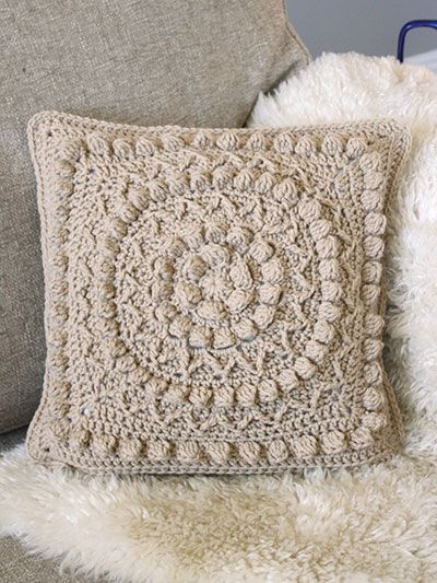 Add a touch of style to your decor with this beautiful crochet pillow cover. Stitch this beautiful pillow using 1 skein of Caron One Pound worsted-weight yarn. The front piece is stitched using sc, sl st, dc, hdc, fptrc, fptrc2tog and dc clusters. The back piece is stitched using all sc.