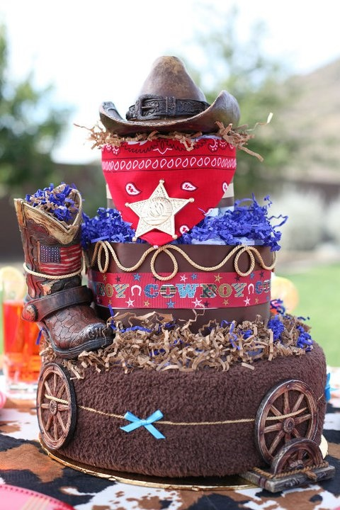 Cowboy inspired diaper cake.   Cake includes: 66 Diapers; 2 9oz Bottles, 1 Brown baby blanket; Cowboy hat piggy bank; Cowboy boot piggy bank; 4 Wagon wheel coasters with holder; 1 Red Bandana; 1 Sheriff Badge. Visit www.creativecouture.org OR www.facebook.com/creativecoutureLLC for more details.