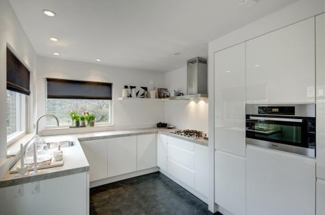 Indeling simpele keuken. Mooi aanrechtblad, mooie rolgordijnen