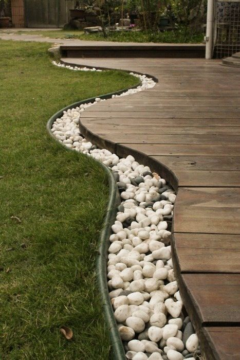 Use rocks to separate the grass from the deck, then bury rope lights in the rocks for lighting