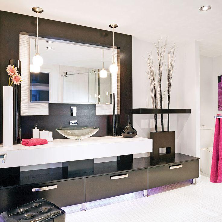 Le blanc et le noir entrent dans la danse pour faire «rocker» cette salle de bain sur une note chic contemporaine. L'alliance des lignes droites du meuble en merisier et du comptoir en stratifié avec les rondeurs sans artifice de la vasque en verre et des luminaires suspendus ajoute au caractère épuré et inédit du décor.
