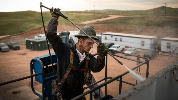WATFORD CITY, ND - JULY 28: Ray Gerish, a floor hand for Raven Drilling, works on an oil rig drilling into the Bakken shale formation on July 28, 2013 outside Watford City, North Dakota. North Dakota has been experiencing an oil boom in recent years, due in part to new drilling techniques including hydraulic fracturing and horizontal drilling. In April 2013, The United States Geological Survey released a new study estimating the Bakken formation and surrounding oil fields could yield up to…