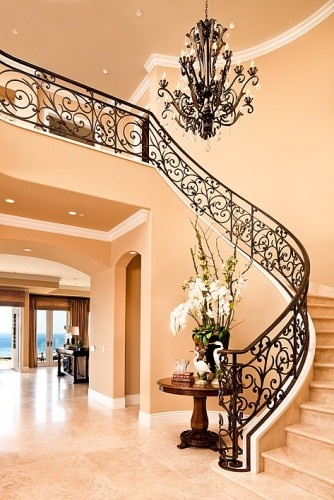 This curved stairway creates a grand entry.  By D for Design www.DforDesignOC.com