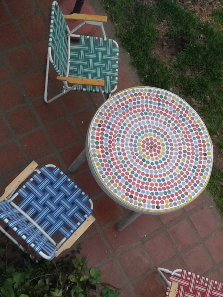 Mesa vieja recubierta con mosaico de tapitas de gaseosa