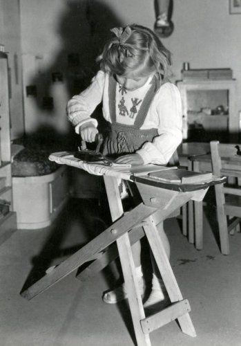 Een schoolmeisje uit het Montessori-onderwijs oefent zich in het strijken met een strijkijzer op een strijkplank. Tentoonstelling 'Schoolstad' in Den Haag, 30 maart 1948.