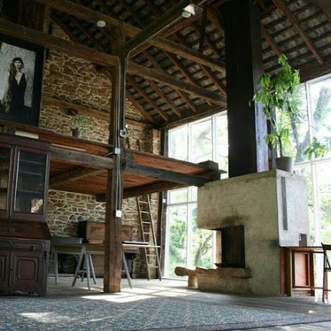 Open loft space with vaulted wood ceilings, stacked stone walls, and floor to ceiling windows